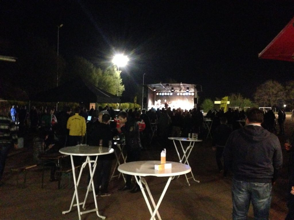 Zuschauer vor einer Bühne, auf der eine Band Rockmusik spielt.